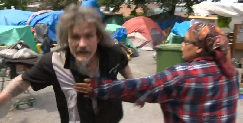 A man at a tent city lunges toward a television cameraman who recorded the encounter. Photograph By CTV Vancouver Island
