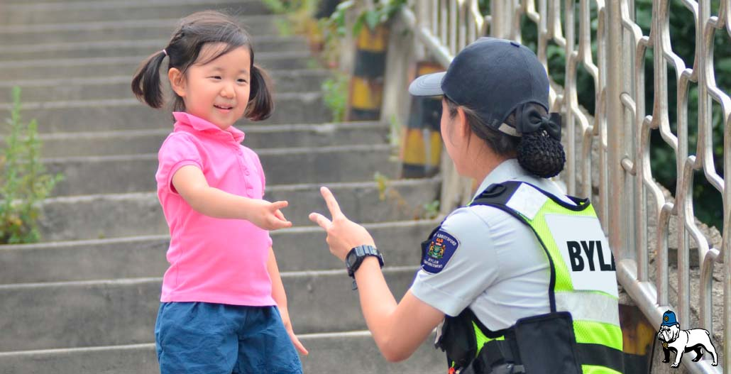 """Female Bylaw Officer playing """"Rock, Paper, Scissors"""" with little girl"""